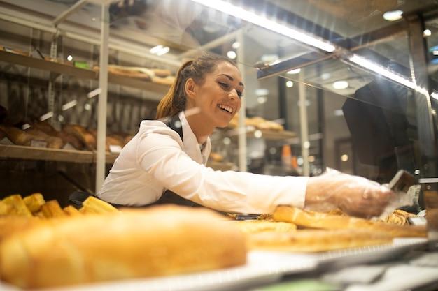 Frau, die brot für verkauf in der supermarktbäckereiabteilung vorbereitet