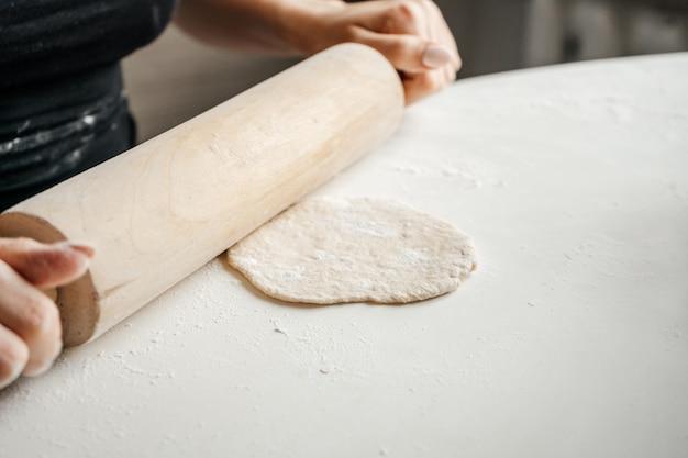Frau, die brotgebäck macht, knetet den teig, der zu hause auf dem küchentisch knetet