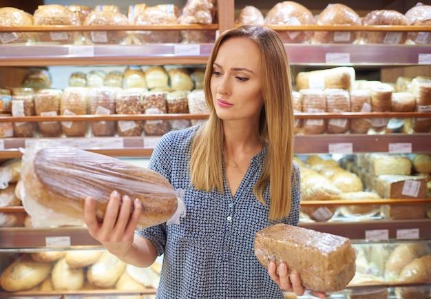 Frau, die brotlaib im supermarkt auswählt