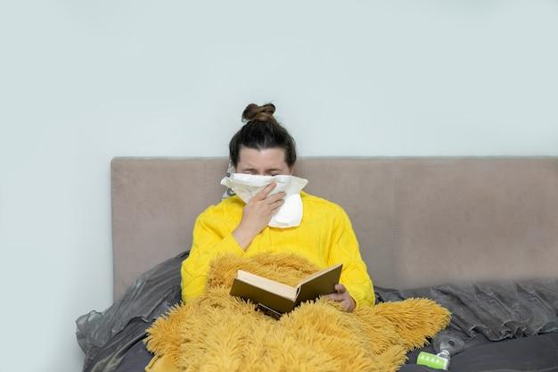 Frau, die buch im bett liest, mit papierserviette niest, erfährt allergiesymptome