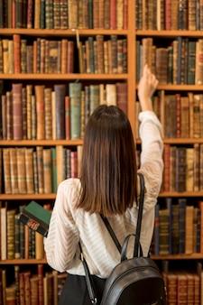Frau, die buch in der bibliothek wählt