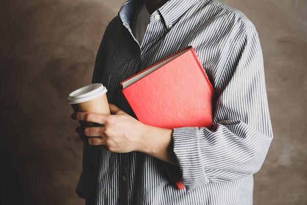 Frau, die buch und kaffee gegen braunen hintergrund, nah oben hält