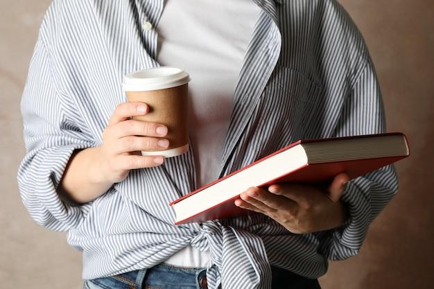 Frau, die buch und kaffee gegen braunen hintergrund, vorderansicht hält
