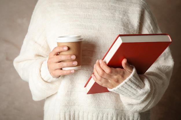 Frau, die buch und kaffee gegen braunen raum, vorderansicht hält