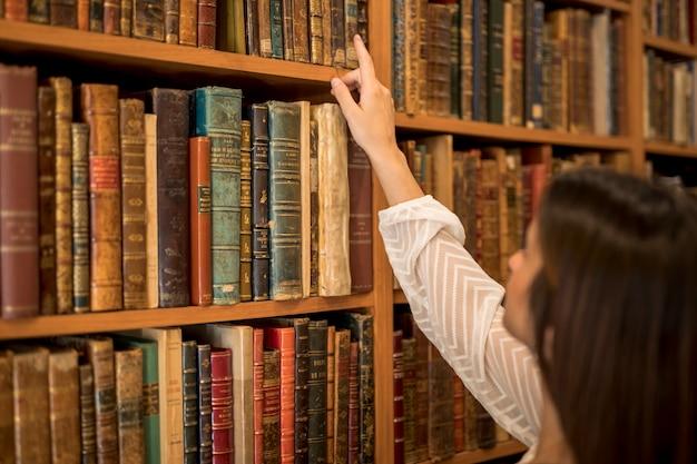 Frau, die buch vom bücherregal in der bibliothek wählt