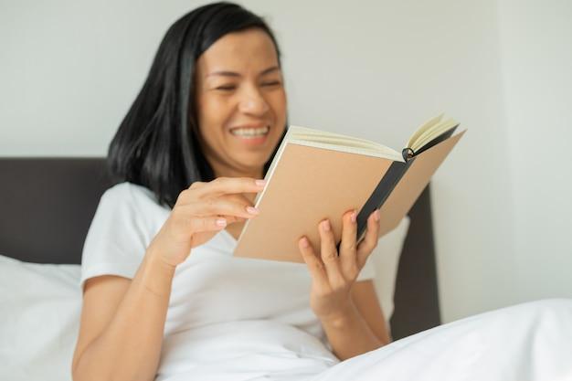 Frau, die buch zu hause im schlafzimmer liest.