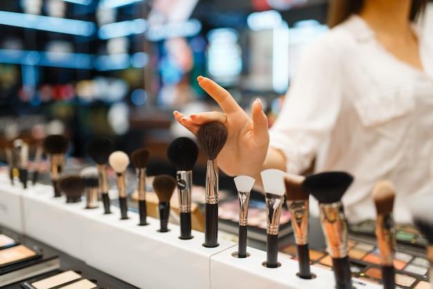 Frau, die bürste am regal im kosmetikgeschäft wählt. käufer an der vitrine im luxus-beauty-shop-salon, kundin im modemarkt