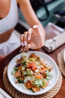 Frau, die bunte gesunde vegane vegetarische mahlzeit salat im sommercafé natürliches tageslicht hat