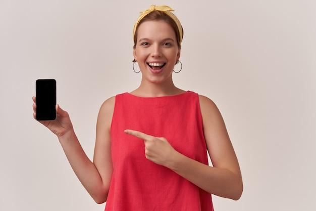 Frau, die buntes outfit und bandana des sommerstils mit natürlichem make-up und ohrringen aufwirft, die wand mit armen halten telefon halten finger nach links zeigen