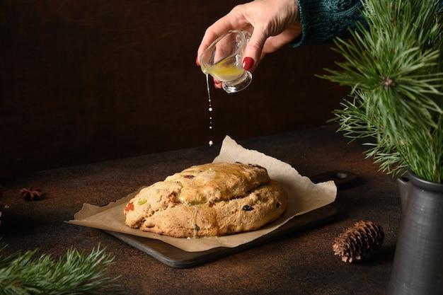 Frau, die butter auf weihnachtsstollen gießt