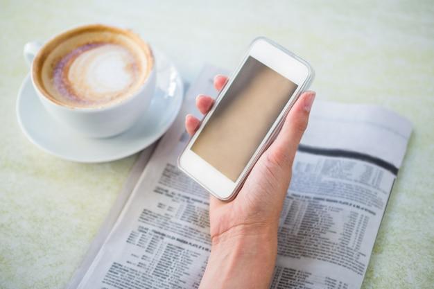 Frau, die cappuccino unter verwendung ihres telefons isst