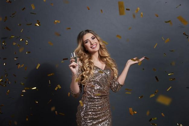 Frau, die champagner trinkt und etwas auf ihrer hand hält