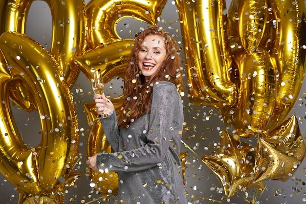 Frau, die champagner unter der dusche von konfetti trinkt