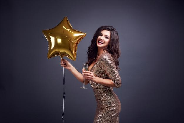 Frau, die champagnerflöte und ballon hält