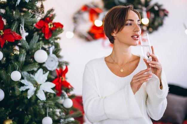 Frau, die champaigne durch weihnachtsbaum trinkt