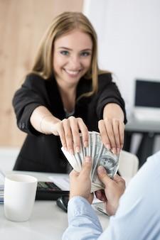 Frau, die charge von hundert dollarnoten nimmt. venalität, bestechung, korruptionskonzept