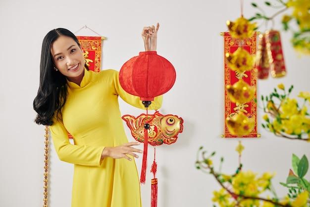 Frau, die chinesische neujahrsdekorationen zeigt