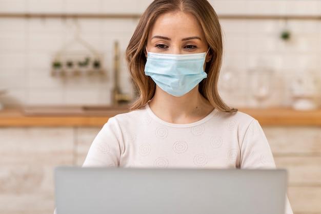 Frau, die chirurgische gesichtsmaske und laptop trägt