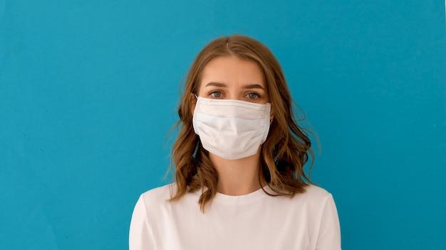 Frau, die chirurgische maske für koronavirus-prävention aufsetzt