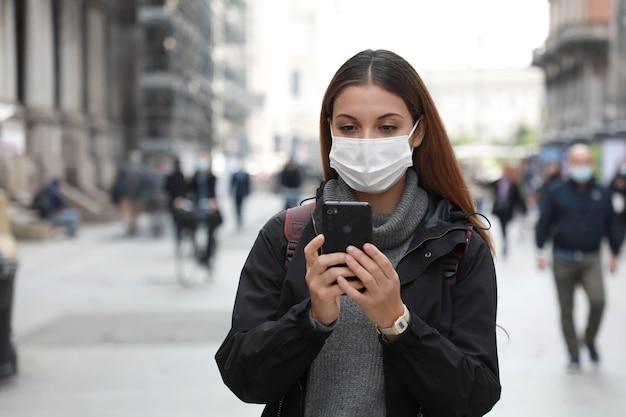Frau, die chirurgische maske mit ihrem handy beim gehen in der straße trägt