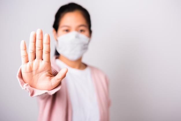 Frau, die chirurgische schutzgesichtsmaske gegen coronavirus ihr angehobenes handstoppschild trägt