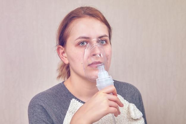 Frau, die copd hat, macht inhalation mit hilfe der verneblerkammer.