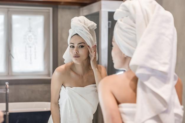 Frau, die creme nach dusche aufträgt