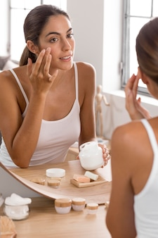 Frau, die creme-selbstpflegekonzept verwendet