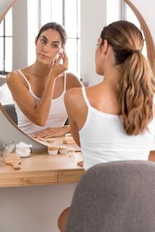 Frau, die creme verwendet und in spiegelselbstpflegekonzept schaut