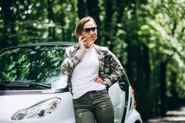 Frau, die das auto im park unter verwendung des telefons bereitsteht