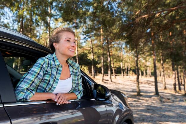 Frau, die das auto in der natur reitet