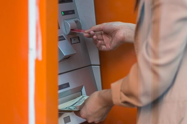 Frau, die das bargeld über atm, geschäfts-automatisches erzähler-maschinenkonzept zurückzieht