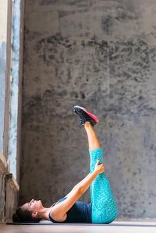 Frau, die das bein ausdehnt übung auf yogamatte tut