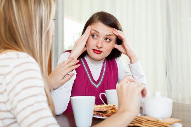 Frau, die das deprimierte mädchen am tisch tröstet