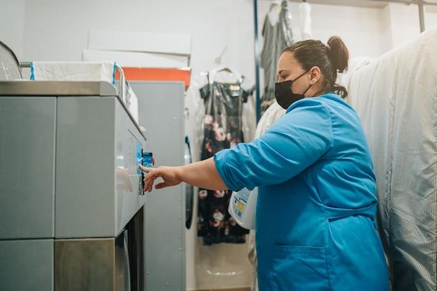 Frau, die das empfindliche programm der industriewaschmaschine setzt