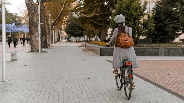 Frau, die das fahrrad von hinten schuss reitet