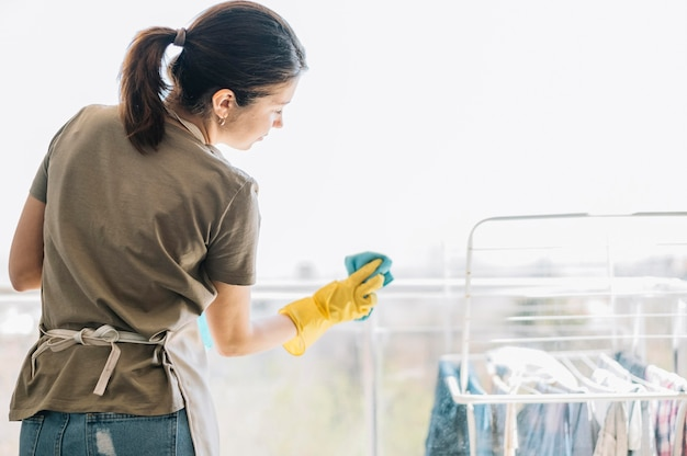 Frau, die das fenster putzt