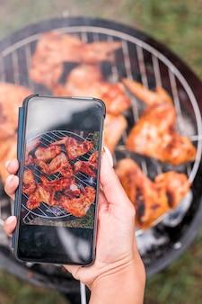 Frau, die das fleisch auf dem grill fotografiert