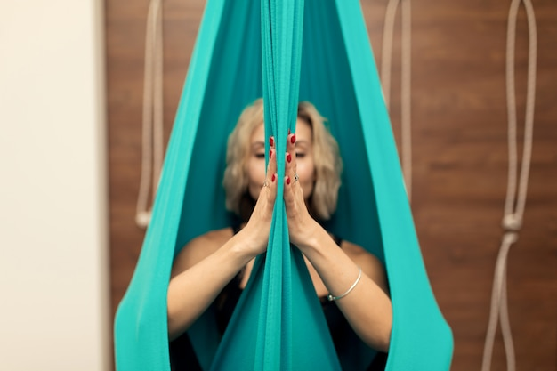 Frau, die das fliegenyoga ausdehnt übungen in der turnhalle tut. fit und wellness lifestyle
