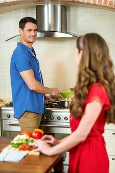 Frau, die das gemüse und mann zu hause kochen auf ofen in der küche hackt