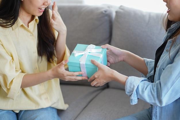 Frau, die das geschenk oder geschenk ihrem freund oder ihrer schwester zum feiern, zum jubiläum und zu den glückwünschen gibt