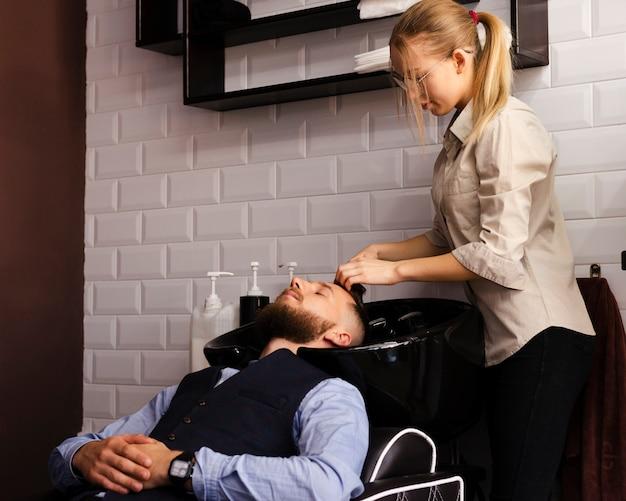Frau, die das haar eines mannes am friseursalon wäscht