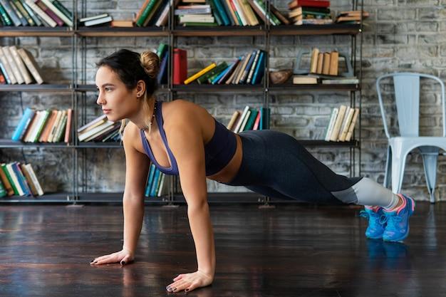 Frau, die das handeln drückt, ups training während des eignungstrainings auf boden zu hause