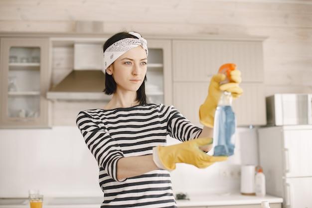 Frau, die das haus in gummihandschuhen hält, die eine sprühflasche halten.