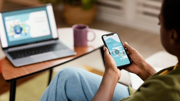 Frau, die das haus mit smartphone und laptop neu dekoriert