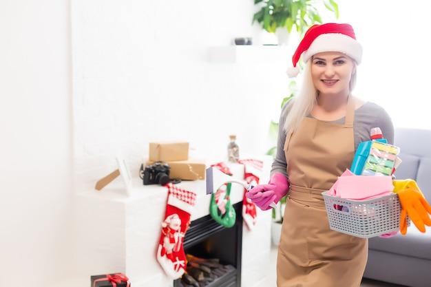 Frau, die das haus säubert lustiges mädchen im sankt-helferhut. weihnachtszeit und hausarbeitskonzept.