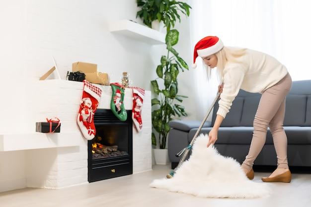 Frau, die das haus säubert lustiges mädchen in sankt-helferhut. weihnachtszeit und hausarbeitskonzept.