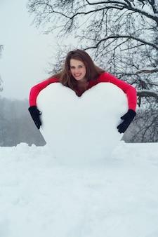 Frau, die das herz vom schnee umarmt