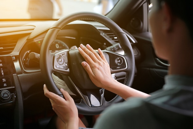 Frau, die das horn beim fahren eines autos durch die straße bedrängt.