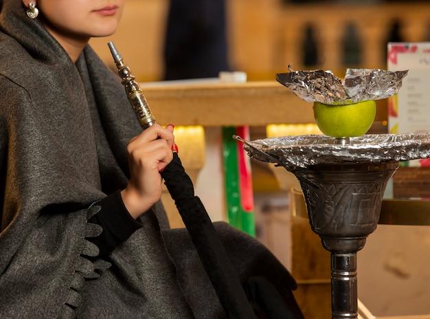 Frau, die das hukarohr sitzt am shisha aufenthaltsraum hält